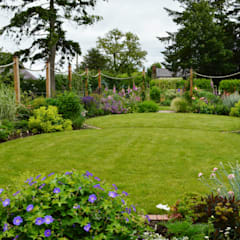 Circular lawns and timber posts support ropes on to which roses and clematis will climb:  Garden by Unique Landscapes