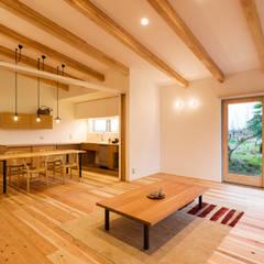居間と台所(新築): エヌ スケッチが手掛けたリビングです。