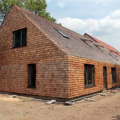 Strawbale kryty dranicą cedrową: styl , w kategorii Domy zaprojektowany przez Organica Design & Build