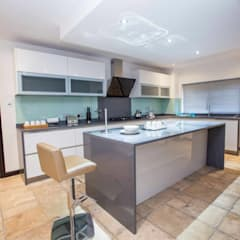 Open plan white gloss kitchen with island:  Kitchen by Schmidt Kitchens Barnet