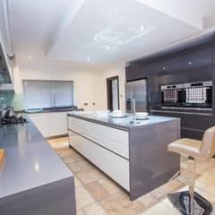 Open plan white gloss kitchen with island:  Kitchen by Schmidt Kitchens Barnet