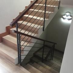 Escalera moldeada con Porcelanato tipo madera: Pasillos y hall de entrada de estilo  por Arquiespacios
