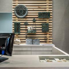 Painel ripado e com objetos para exposição de acessórios: Lojas e imóveis comerciais  por Andresa Jessita