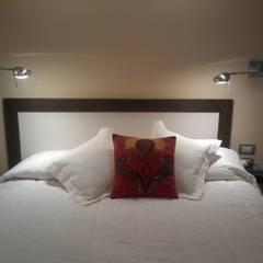 Detalle de cabecera de cama apoyada sobre tabique divisor y de los artefactos iluminación tipo apliques móviles.: Dormitorios de estilo  por D&C Interiores