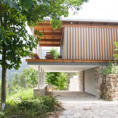 acesso à garagem sob a casa: Casas  por A+ arquitectura