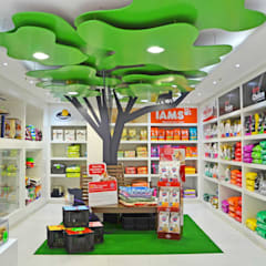 Shop interior with 'park themed' tree, bench & animals:  Commercial Spaces by Till Manecke:Architect