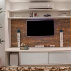Detalhe do painel da Tv com tijolinho : Salas multimídia  por Carolina Fontes Arquitetura
