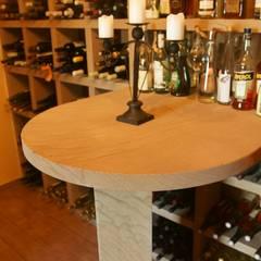 Weinregal mit Tisch aus Sandstein in Lauterbach: rustikaler Weinkeller von BOOR Bäder, Fliesen, Sanitär