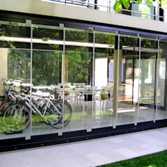 Garaje protegido con Cortinas de Cristal (Paneles Corredizos de Vidrio): Jardines de invierno de estilo moderno por AIRCLOS