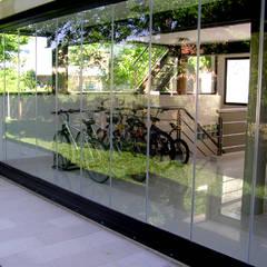 Garaje protegido con Cortinas de Cristal (Paneles Corredizos de Vidrio): Jardines de invierno de estilo  por AIRCLOS, Moderno