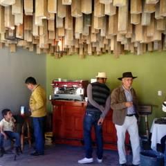 Vista de cafeteria en funcionamiento y falso plafón por medio de polines colganteados.: Estudios y oficinas de estilo rural por taller garcia arquitectura integral