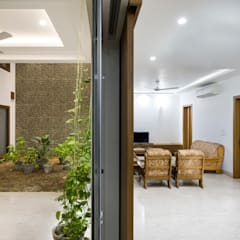 Living and Dining Space of the house at equilibrium with the internal courtyard.:  Living room by Manuj Agarwal Architects