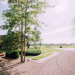 Uitzicht vanuit woning naar omliggende landschap: landelijke Tuin door Buro Buitenom exterieurontwerpers