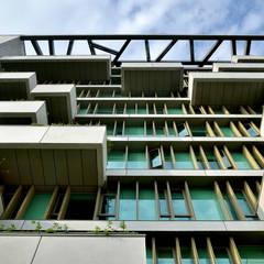 以模矩交錯設置的GRC清水混凝土外牆板、垂直遮陽板及屋頂碎冰文分割之爬藤屋架。:  牆面 by 綠野國際建築師事務所