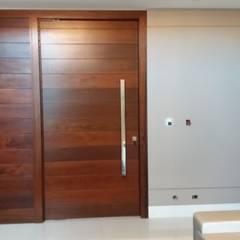 Porta Pivotante em madeira: Corredores e halls de entrada  por MEI Arquitetura