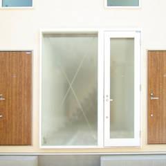 板橋の重層長屋: 有限会社東風意匠計画が手掛けた玄関ドアです。,モダン ガラス