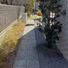 自然石のシンプルな路地: 有限会社東風意匠計画が手掛けたアプローチです。