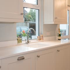 Quartz worktops with matching upstands and window sills add a uniform look:  Built-in kitchens by ADORNAS KITCHENS