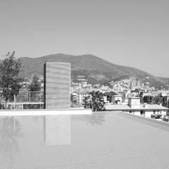 piscina: Piscina a sfioro in stile  di ariu + vallino architetti