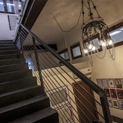 Scala in ferro verniciato grezzo, lampadario degli anni '30 in ferro battuto, realizzato nell'azienda stessa.: Spazi commerciali in stile  di Officine Locati
