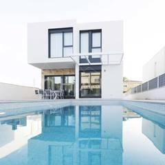 Fachada posterior con vistas al jardín y piscina.: Casas prefabricadas de estilo  de Casas inHAUS