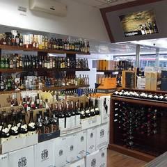 Adega modelo balcão em loja de vinhos: Espaços comerciais  por Edr Cristal - Adegas Climatizadas