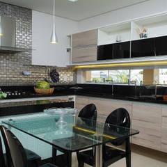 Cozinha com ilha: Armários e bancadas de cozinha  por Bernal Projetos