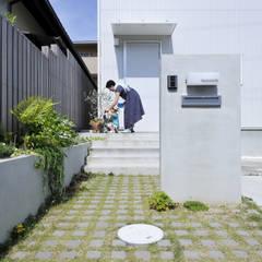 植栽がお出迎え。緑あふれるアプローチ: タイコーアーキテクトが手掛けた一戸建て住宅です。