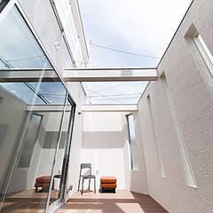 中庭とカーテンのいらないリビングの家: コンフォート建築設計工房が手掛けたサンルームです。