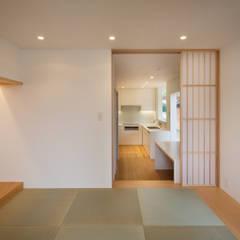 平屋と二階建てが土間で繋がる二世帯住宅: 有限会社角倉剛建築設計事務所が手掛けた和室です。,モダン