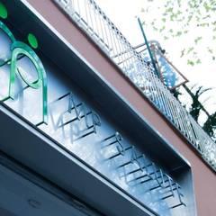 L'insegna retroilluminata, disegnata dallo studio: Ingresso & Corridoio in stile  di VITAE DESIGN studio di architettura