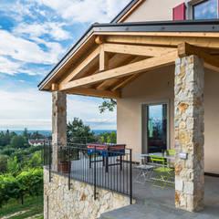 Stile collinare: Casa unifamiliare in stile  di Woodbau Srl