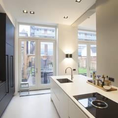 Keuken met zwarte kastenwand en wit eiland:  Inbouwkeukens door Thijssen Verheijden Architecture & Management