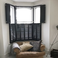 Amazing statement shutters in North London.:  Living room by Plantation Shutters Ltd