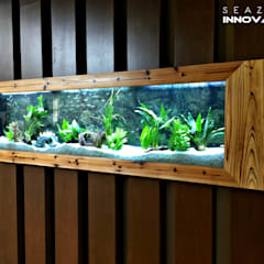 Placing an wall mounted aquarium near the front entry is an easy and inexpensive way to add a dose of eye-catching color. The colorful fishes and natural plants cheerfully leads visitors inside.:  Commercial Spaces by Seazone Innovative Sdn Bhd