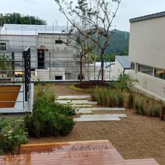 Jardines en la fachada de estilo  por (주)더숲