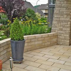 Eine Gartenanlage verbindet moderne und natürliche Linien.:  Terrasse von RAUCH Gaten- und Landschaftsbau GbR
