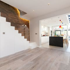Minimalist hallway with white staircase leading through to open-plan kitchen:  Stairs by Timothy James Interiors