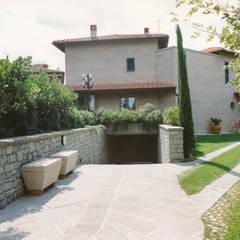 rampa di accesso all garage coperto perfettamente integrata del progetto: Posto auto coperto in stile  di Morelli & Ruggeri Architetti