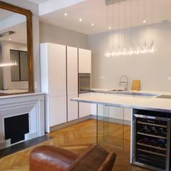 Cuisine ouverte sur un petit salon et sa cheminée : Cuisine intégrée de style  par RB CONCEPT