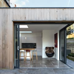 Pocket doors open the kitchen out to the garden:  Houses by Hetreed Ross Architects