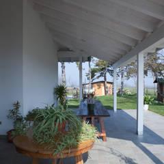 Porticato aperto sul lato della casa: Terrazza in stile  di Spazio Positivo