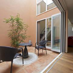 中庭を愛でるガレージハウス: 余田正徳/株式会社YODAアーキテクツが手掛けた庭です。,地中海 石