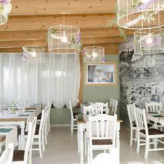 """restyling ristorante pizzeria """"da Rina"""".un ambiente dove i colori, le forme e gli arredi si fondano con l'arte culinaria: Negozi & Locali commerciali in stile  di msplus architettura"""
