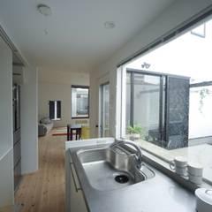 キッチンから光庭を眺められます: 石川淳建築設計事務所が手掛けたシステムキッチンです。
