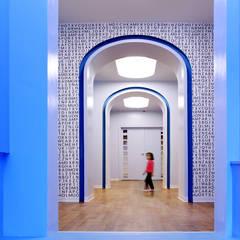 Vista do interior do corredor da galeria de acesso ao espaço criança.: Espaços comerciais  por Estúdio AMATAM