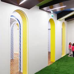 Vista do interior do corredor para o acesso ao espaço lúdico.: Espaços comerciais  por Estúdio AMATAM