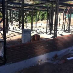 vista de instalación de muros de albañilería entre pilares metálicos: Casas de estilo  por MAC SPA