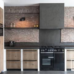Keuken met betonstuc en steense wand: industriële Keuken door Molitli Interieurmakers