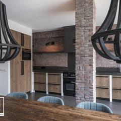 Keuken met betonstuc en steense wand:  Keuken door Molitli Interieurmakers